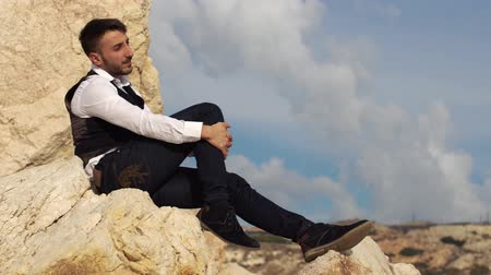 skalní útes : Handsome stylish man sit on the rocks and waching an amazing view. Cyprus. Paphos