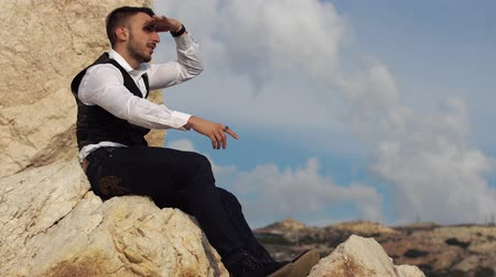 descobrir : Handsome stylish man in fancy cloth sitting on the rocks and waching an amazing view while showing something to people with his finger. Cyprus. Paphos Vídeos