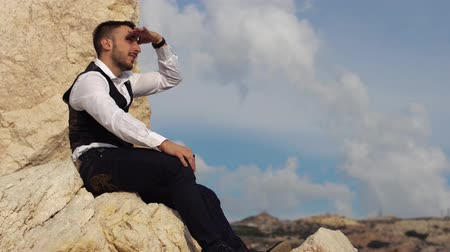 cipro : Handsome stylish guy sitting on the rocks and peers into the distance. Cyprus. Paphos