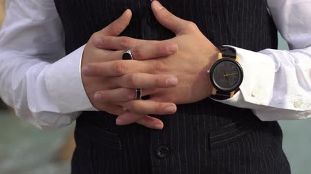 think big : Crossed fingers of stylish man in a white shirt close up. Stylish watch on the hand of the big boss.
