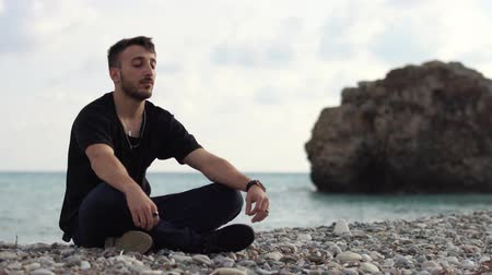 time laps : Young man with closed eyes sitting and relaxing in yoga style near amazing sea side view. Handsome guy meditating on the background of a rock and the sea. Time laps. Cyprus. Paphos