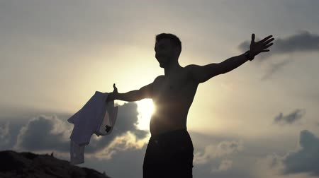 saborear : Young man shirt off shouts freedom and clapping hands in high hill of mountain in sunset. Man throwing his hands byside, enjoying freedom, believe future success. Happy tourist on rock top, victory and purpose. Vídeos