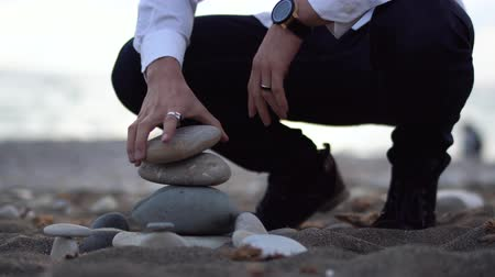 descobrir : Man on the beach try to build a pyramid with grey stones but its not easy, stones fall down.