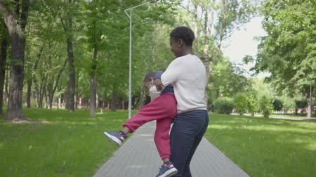 пикник : African American mother is spinning her son in her arms. Mom and child spend the weekend relaxing in the park.