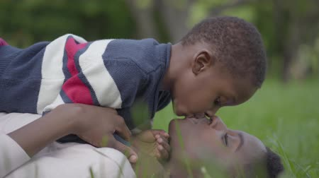 back side : Close-up view of pretty African American woman lying on the grass in the park, her little son lying on top of her and kissing woman. Mother and boy resting outdoors. Motherhood concept, family love Stock Footage