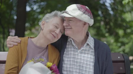 aposentar : Portrait of a mature couple in love sitting on a bench in the park. Adult woman holds a beautiful bouquet of flowers while her elderly husband hugs her. Tender relationship adult couple outdoors. Stock Footage