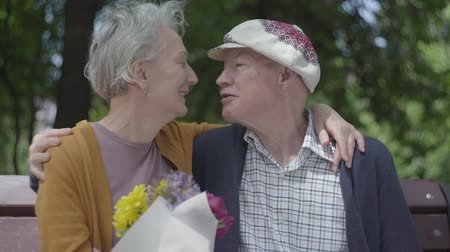 aposentar : Adult woman holds a beautiful bouquet of flowers while her elderly husband hugs her. Tender relationship adult couple outdoors.