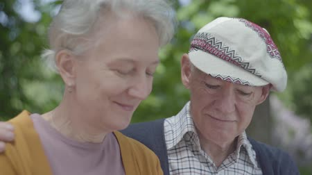 aposentar : Portrait of a mature couple in love sitting on a bench in the park. Adult woman and elderly husband. Tender relationship adult couple outdoors. Stock Footage