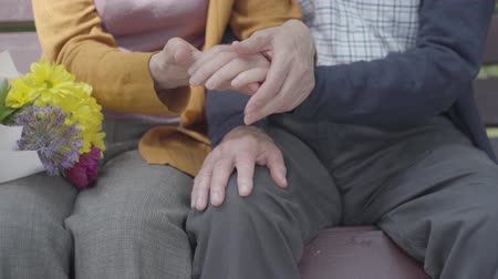 rebuliço : Close up hands of mature people. Hands of an old woman holding the hand of old man. Tender relationship adult couple outdoors.