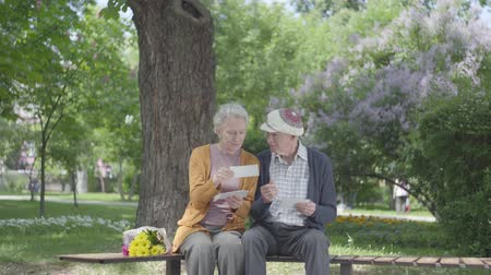 resimlerinde : Portrait adorable adult couple looking old photos remembering happy moments sitting on a bench in the park. Mature couple in love resting on a sunny warm spring day outdoors.