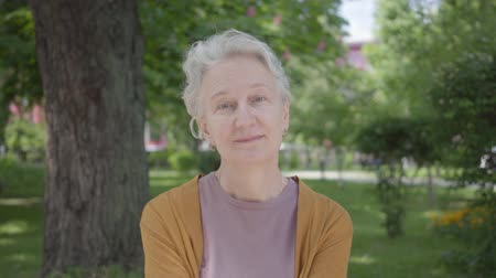 запомнить : Portrait of cute old woman with grey hair smiling in the green amazing park. Adorable mature grandmother resting on a sunny warm spring day outdoors. Changing emotions on the face of a woman Стоковые видеозаписи
