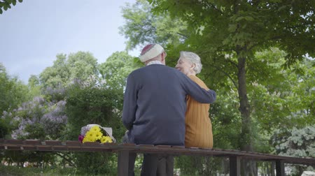 emekli olmak : Back of old man sit in the bench in the park with bouquet of yellow flowers and hug woman with grey hair. Woman put her head on males shoulder Stok Video