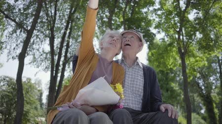 引退する : Portrait of a mature couple in love sitting on a bench in the park. Adorable woman and old man together. Tender relationship adult couple outdoors.
