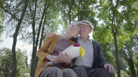 emekli olmak : Portrait of a mature couple in love sitting on a bench in the park. Adult woman holds a beautiful bouquet of flowers while her elderly husband hugs her. Tender relationship adorable couple outdoors.