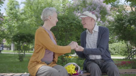 шестидесятые годы : Old woman with bouquet of yellow flowers sitting with an old man and holding hands in the bench in the park. Tender relationship adult couple outdoors.
