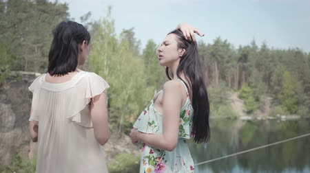 支出 : Portrait two charming young women wear summer dresses standing in the top of rock and looking at amazing view of nature. Cute girls walk outside the city. Adorable girlfriends spending weekend togethe