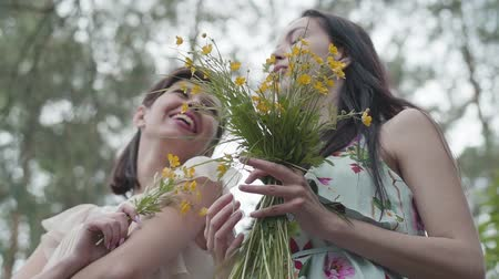 rövid : Two beautiful women standing in the forest with amazing wild flowers. Slow motion.