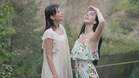 deep autumn : Two beautiful woman in short white dresses standing aroung amazing nature, looking in the sky. Spectacular view. Slow motion.