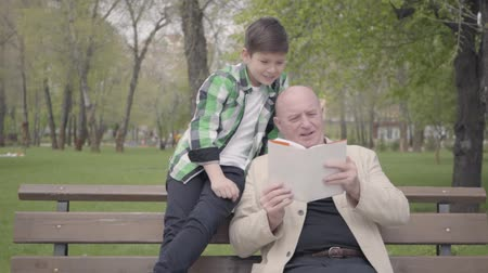 шестидесятые годы : Portrait cute grandfather and adorable grandson sitting in the park on the bench, old man reading the book for the boy. Generations concept. Friendly family. Leisure outdoors. Grandpa and grandson