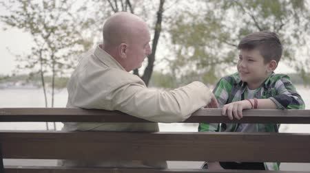 stary : Portrait grandfather and grandson sitting in the park near the river on the bench, old man telling interesting story to the boy, the child listening attentively. Generations concept. Friendly family. Leisure outdoors Wideo