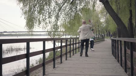 dech : Little boy running away from his grandfather on the wooden bridge near the river. The old man was tired and stopped to catch his breath. Family playing outdoors Dostupné videozáznamy