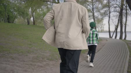 invite : Little boy running away from his grandfather in the park. The old man chasing the boy, but he is tired and stopped to catch his breath. Family playing outdoors
