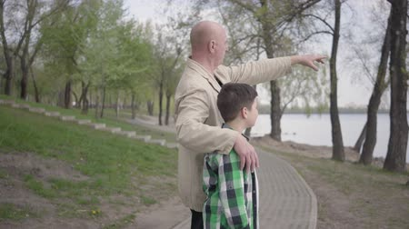 hayran olmak : Grandfather and grandson standing on riverbank, looking on the water, pointing into distance. The man hugs the child by his shoulders. Generations concept. Summertime leisure. Connection with nature Stok Video