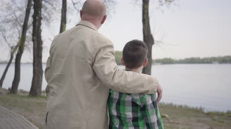 benzer : Grandfather and grandson standing on riverbank, looking on the water, pointing into distance. The man hugs the child by his shoulders. Generations concept. Summertime leisure. Connection with nature Stok Video