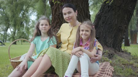 3 : Mature woman sitting on the grass under the tree in the park with two cute granddaughters, looking in camera and smiling. Happy family spending time outdoors 動画素材