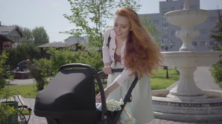 ohnutý : Adorable red-haired mom bent over a pram and smiling in the park. Cute woman enjoying the sunny day with her baby outdoors. Young mother walking with a child