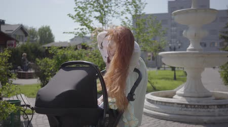 wozek dzieciecy : Beautiful red-haired woman bent over a pram and smiling in the park. The lady enjoying the sunny day with her baby outdoors. Young mother walking with a child Wideo