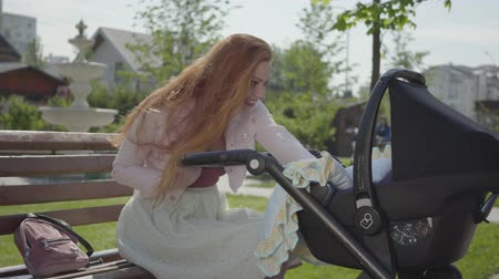 szülői : Young happy redhead mother sitting on bench near the house with baby carriage and smiling and speaking to him on a nice spring day Stock mozgókép