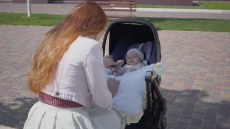 urlop : Beautiful red-haired woman playing with her kid lying in the pram in the park. The lady enjoying the sunny day with her baby outdoors. Young mother with a child. Happy family