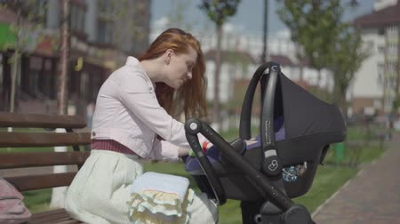 出生前の : Red-haired woman playing with her kid lying in the pram in the park close-up. Mom enjoying the sunny day with her baby outdoors. Young mother with a child. Happy family 動画素材