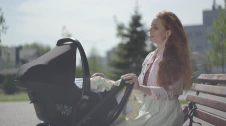 urlop : Young happy redhead mother sitting on bench near the house with baby carriage and smiling and lulling him on a nice spring day Wideo