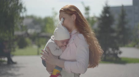 szülői : Young beautiful redhead mother holding a cute baby in her arms and talking to him in a spring sunny day. Happy family.