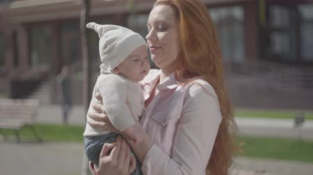 szülői : Portrait young cute beautiful redhead mother holding a adorable baby in her arms and talking to him in a spring sunny day. Mom with a child outdoors. Happy family. Stock mozgókép