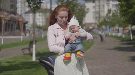 urlop : Young beautiful redhead mother holding a cute baby boy in her arms and talking to him in a spring sunny day. Mom with a child outdoors. Happy family.