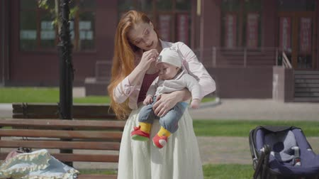 wozek dzieciecy : Portrait pretty red-haired woman playing with her child sitting on the bench. The stroller standing near. The lady enjoying the sunny day with her baby outdoors. Young mother with a kid. Happy family