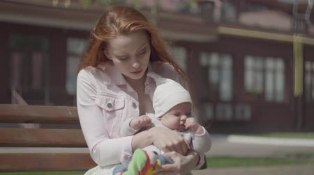 urlop : Portrait of a beautiful red-haired woman playing with her child sitting on the bench close-up. The lady enjoying the sunny day with her baby outdoors. Young mother with a kid. Happy family.