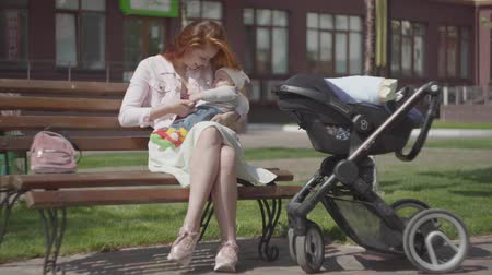 bank : Beautiful red-haired woman playing with her child sitting on the bench. The stroller standing near. The lady enjoying the sunny day with her baby outdoors. Young mother with a kid. Happy family.