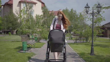 оставлять : Young happy redhead mother walking with baby carriage and smiling along the street on a nice spring day