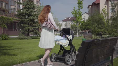 urlop : Beautiful red-haired woman walking on the walking along a stone walkway with a pram in the park. The lady enjoying the sunny day with her baby outdoors. Young mother walking with a child