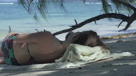 hurma ağacı : Seychelles. Praslin Island. Young girl lying in the shade of palm trees listens to music on the shores of an exotic island located in the Indian Ocean. Tropical island luxury vacation. Stok Video