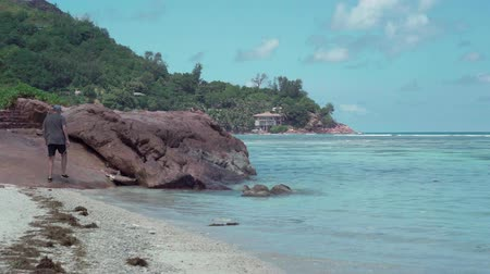 praslin : Seychelles. Praslin Island. Beautiful landscape. Seawater rolls on the beach. Small houses hidden in the trees by the sea. Back view of the man climbing the rocks. Tourism, vacation, traveling concept