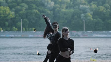 ustalık : Skillful man and two women in black clothes and masks perform a show with flame while standing on riverbank. Skillful fireshow artists showing mastery of juggling and motion of fire in the evening