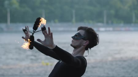 ustalık : Portrait skillful young slim man in black clothes and mask performing a show with flame standing on riverbank. Professional fireshow artist showing mastery of juggling and motion of fire in the evening Stok Video
