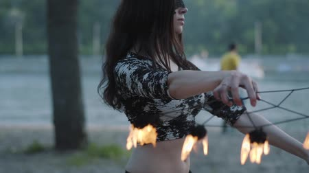 awesome : Portrait of grace woman in mask performing a show with flame standing on riverbank in front of trees. Skillful fireshow artist showing dancing with fire fans in the evening. Slow motion