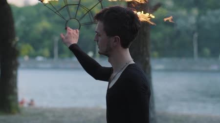 ustalık : Portrait of young professional man performing a show with fire fan standing on riverbank in front of trees. Skillful fireshow artist dancing with fire fans in the evening. Slow motion