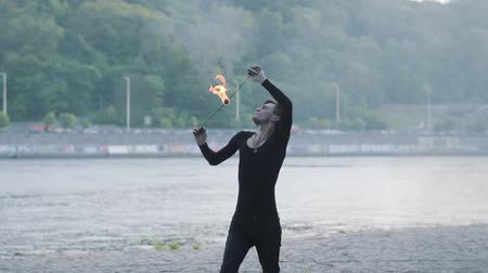 jet out : Young man in black clothes performing a show with flame standing on riverbank. Skillful fireshow artist exhaling powerful fiery jet in the evening. Slow motion. Male breathes out large stream of fire